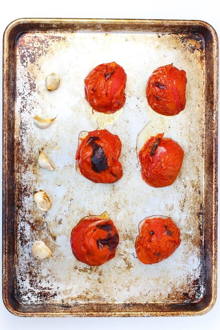 charred tomatoes and garlic on a sheet pan