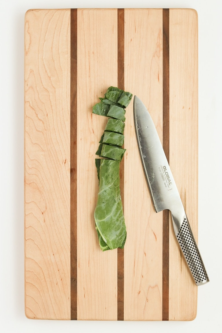 collard green leaf rolled up and cut into 1-inch pieces on a cutting board with chef's knife.