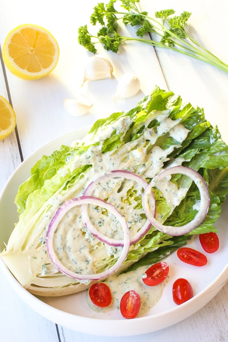 Romaine lettuce wedge with ranch dressing, red onions slices, slices cherry tomatoes, lemon, garlic and parsley