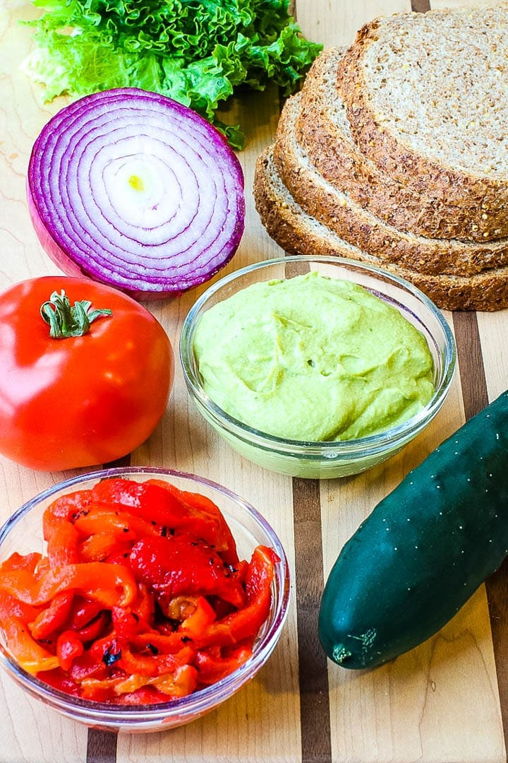 spicy hummus on a cutting board with bread, tomato, red onion, red peppers, cucumber and lettuce