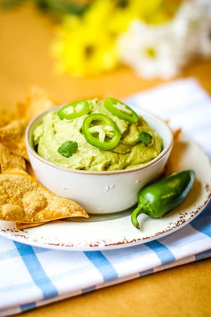 Spicy oil free hummus in a bowl with tortilla chips and jalapeño on a blur plaid towel with daisies