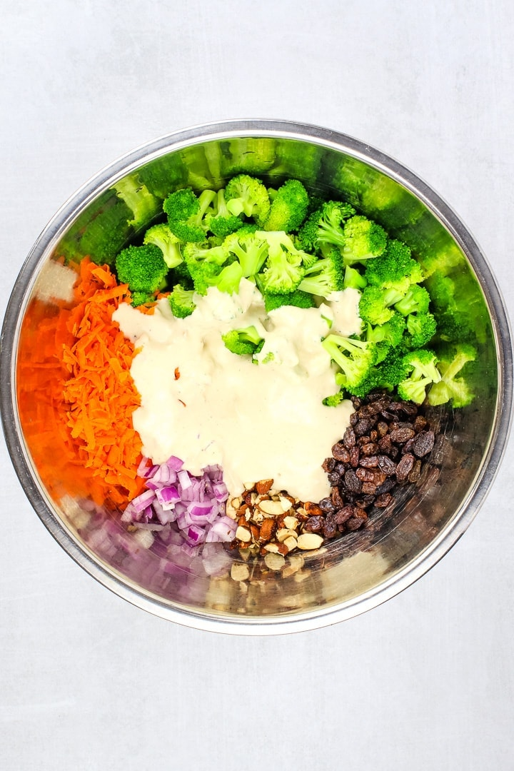 metal mixing bowl with blanched broccoli, shredded carrots, diced red onion, raisins, smoky almonds and sweet & creamy dressing.