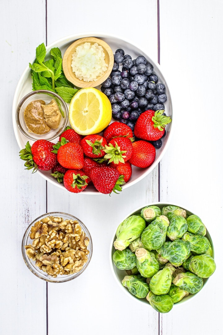 salad ingredients in bowls: strawberries, blueberries, lemon, miso paste, almond butter, mint leaves, diced shallot, brussels sprouts and walnuts
