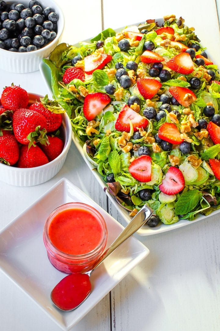 Shaved brussels sprouts, sliced strawberries, blue berries, mint leaves chopped walnuts on a bed of spring greens on a white platter with strawberry vinaigrette in a jar and bowls of berries.