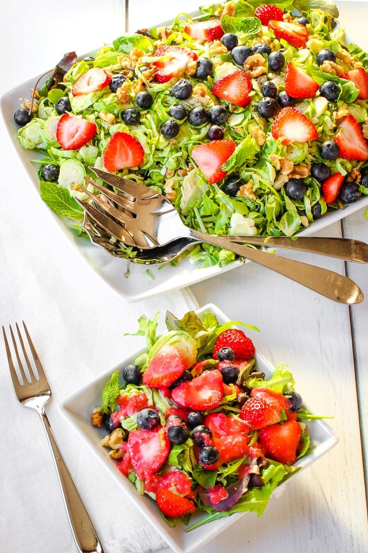 Shaved brussels sprouts, sliced strawberries, blue berries, mint leaves chopped walnuts on a bed of spring greens on a white platter with a small plate of salad and a fork