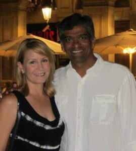 Elizabeth Shah in a black dress and Hemant Shah in a white shirt, in a square in Barcelona