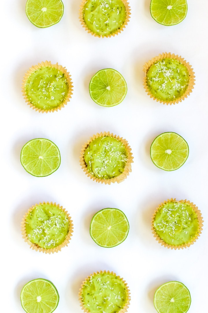 overhead shot of vegan key lime pie mini tarts and cut limes on a white background