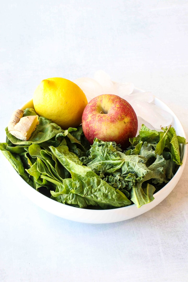 Green smoothie ingredients in a white bowl-apple, lemon, kale, spinach, ginger and ice cubes