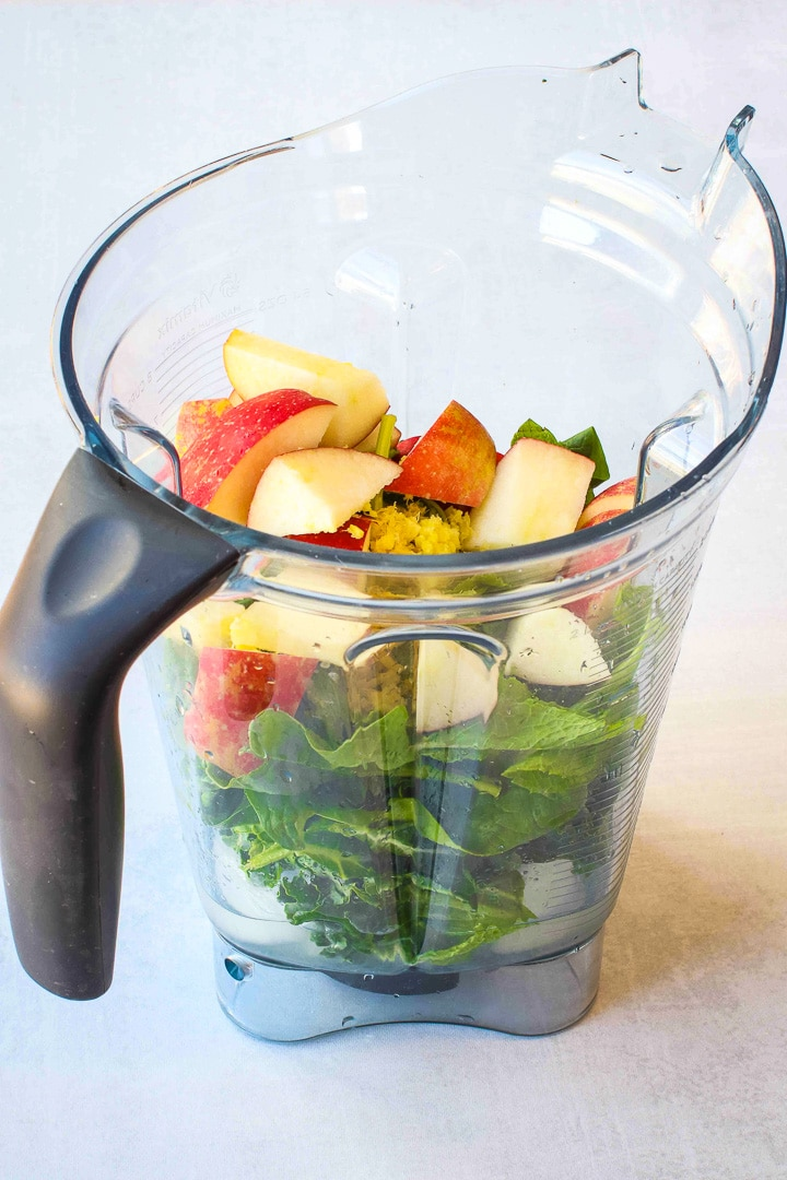 Green smoothie ingredients in a blender-apple, lemon, kale, spinach, ginger and ice cubes