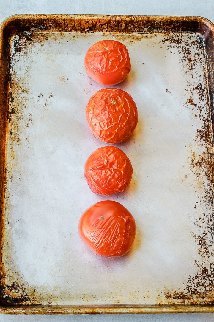 4 Tomatoes with wrinkled skins on a sheet pan.