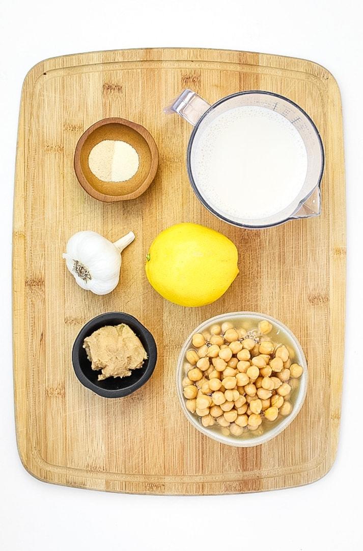 vegan alfredo sauce ingredients on a cutting board, chickpeas, lemon, garlic, plant milk, miso paste, garlic and onion powder