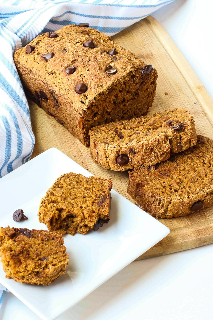 pumpkin chocolate chip bread on cutting board with blue striped towel