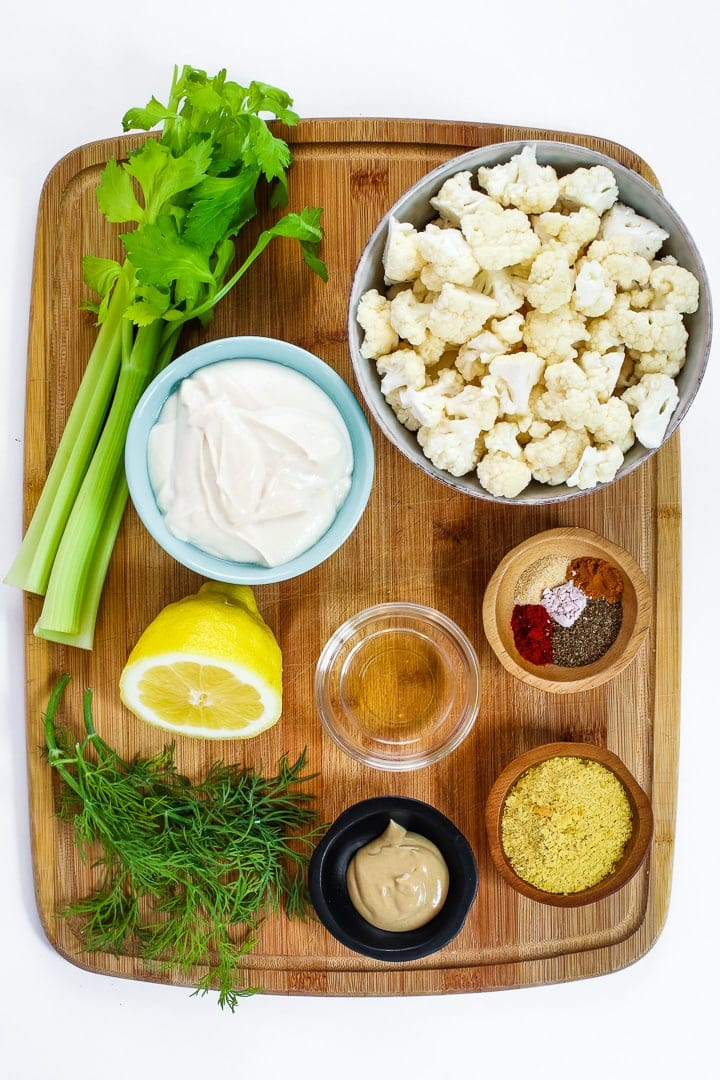 cutting board with celery, cauliflower florets, bowl of mayo, lemon half, dill sprigs, vinegar, dijon mustard, nutritional yeast and spices.