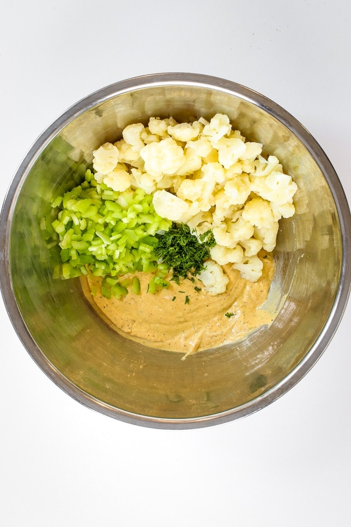 stainless steel mixing bowl of dark yellow dressing, diced celery, cauliflower florets and chopped dil