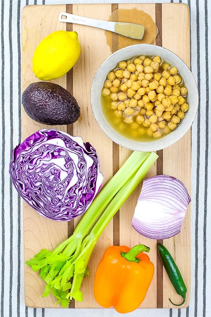 Bowl of chickpeas, lemon, tahini, celery, red onion half, purple cabbage half, avocado, orange bell pepper and serrano pepper on a striped wood cutting board on a black and white striped linen towel.