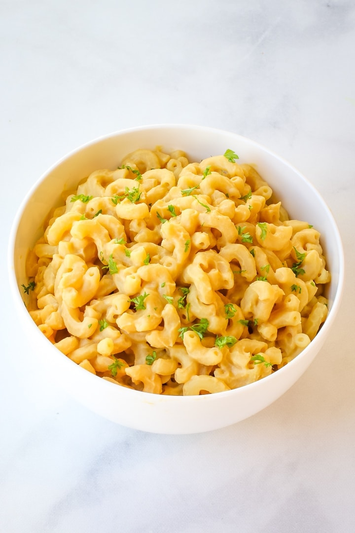 Elbow macaroni and creamy chickpea cheese sauce in a white bowl on white marble, topped with herbs.