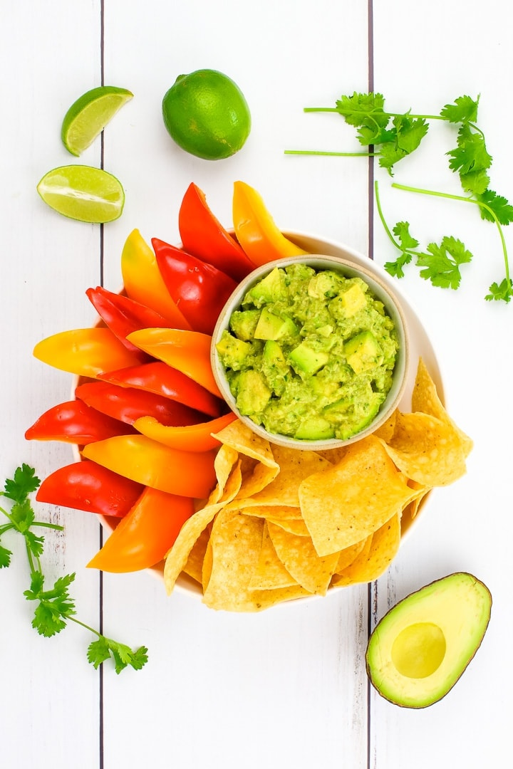 Chunky vegan guacamole in a bowl on a platter of baked tortilla chips and red & orange bell pepper slices, surrounded by Limes, cilantro & avocado.