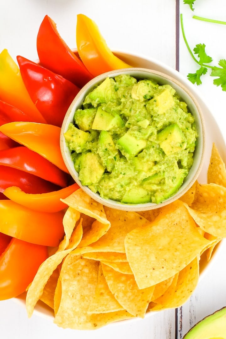 Close up of chunky vegan guacamole in a bowl on a platter of baked tortilla chips and red & orange bell pepper slices, surrounded by cilantro & avocado.