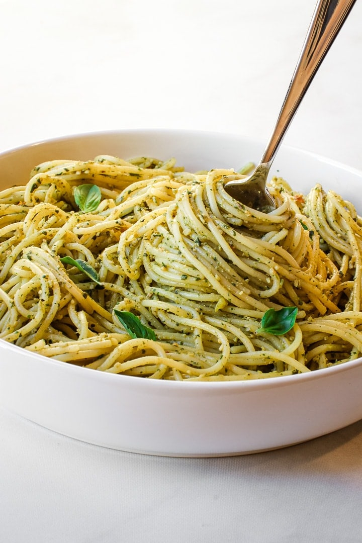White bowl of spaghetti with pesto sauce and basil leaves with a pasta-filled twirling fork on marble.