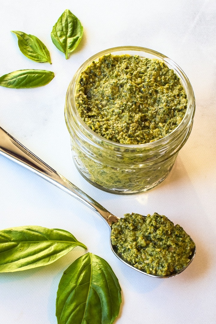 Jar of pesto and spoon of pesto with basil leaves on marble.