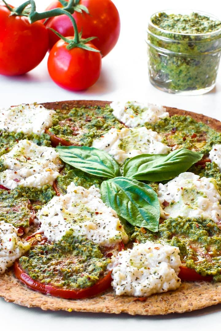 Thin crust pesto pizza with sliced tomatoes, fresh almond ricotta, seasonings and 3 basil leaves in center. Vine tomatoes and jar of pesto in background.