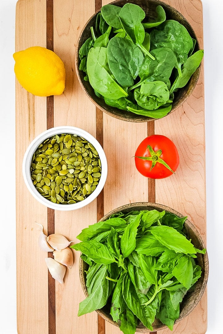 Striped cutting board with wooden bowls of spinach and basil, a lemon, tomato, garlic, and a white bowl of pepitas.