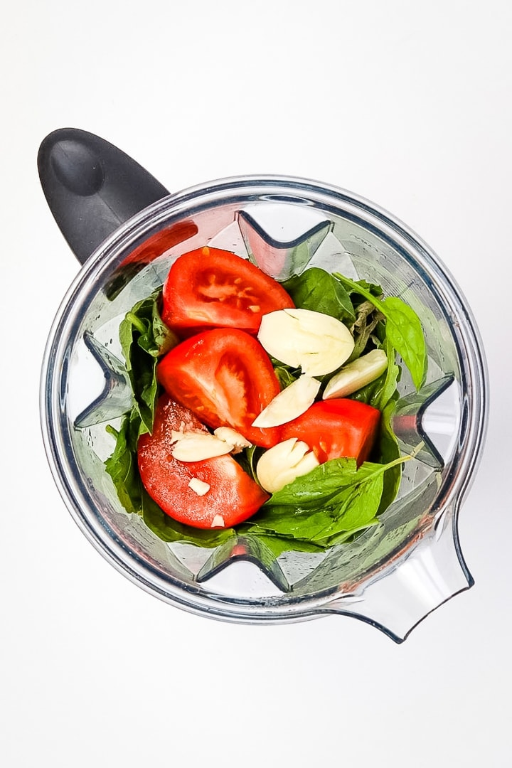 Overhead shot of blender with tomatoes, garlic, basil and spinach.