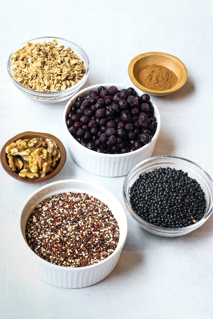 small bowls on a gray background with frozen blueberries, tricolored quinoa, walnuts, black lentils, cinnamon and granola