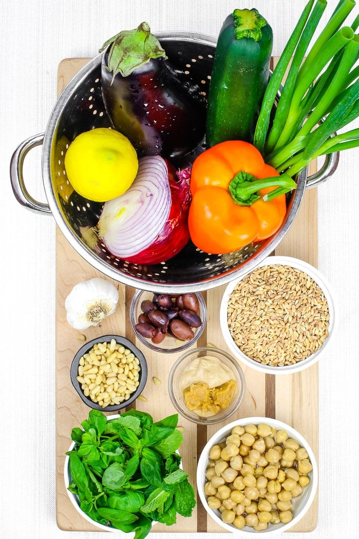 Ingredients on a cutting board. Roast vegetable salad with eggplant, orange peppers zucchini, olives, red onions, garlic, green onions, farro, pine nuts, chickpeas, basil, and lemon.