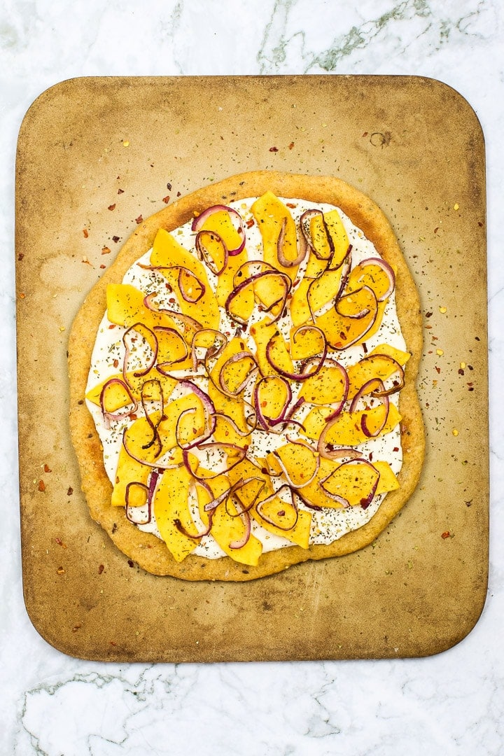Roasted squash white pizza on pizza stone on white marble.