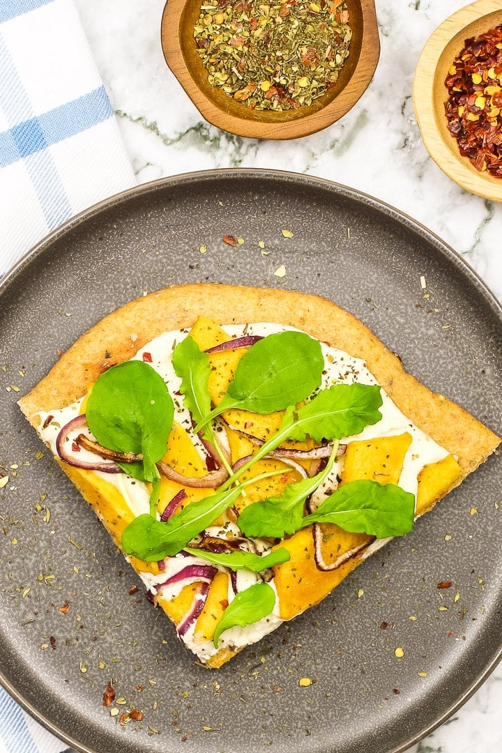 roasted squash white pizza topped with arugula on a gray plate. Little dishes of Italian seasonings and cursed red peppers, blue plaid towel and marble.