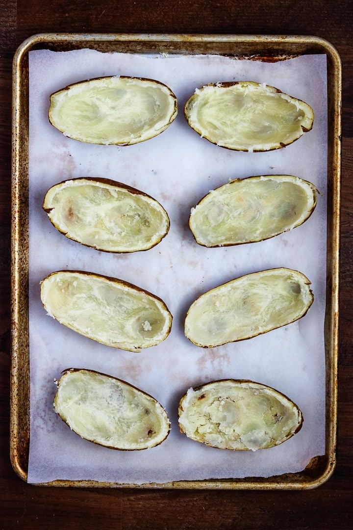Scooped out baked potato shells on a parchment paper lined sheet pan.