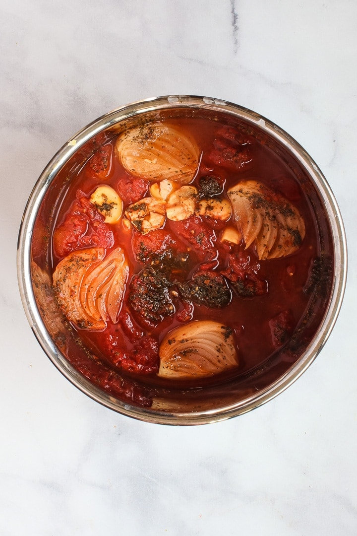 Instant Pot pot with cooked ingredients: tomatoes, quartered onion, smashed garlic cloves and Italian seasonings.