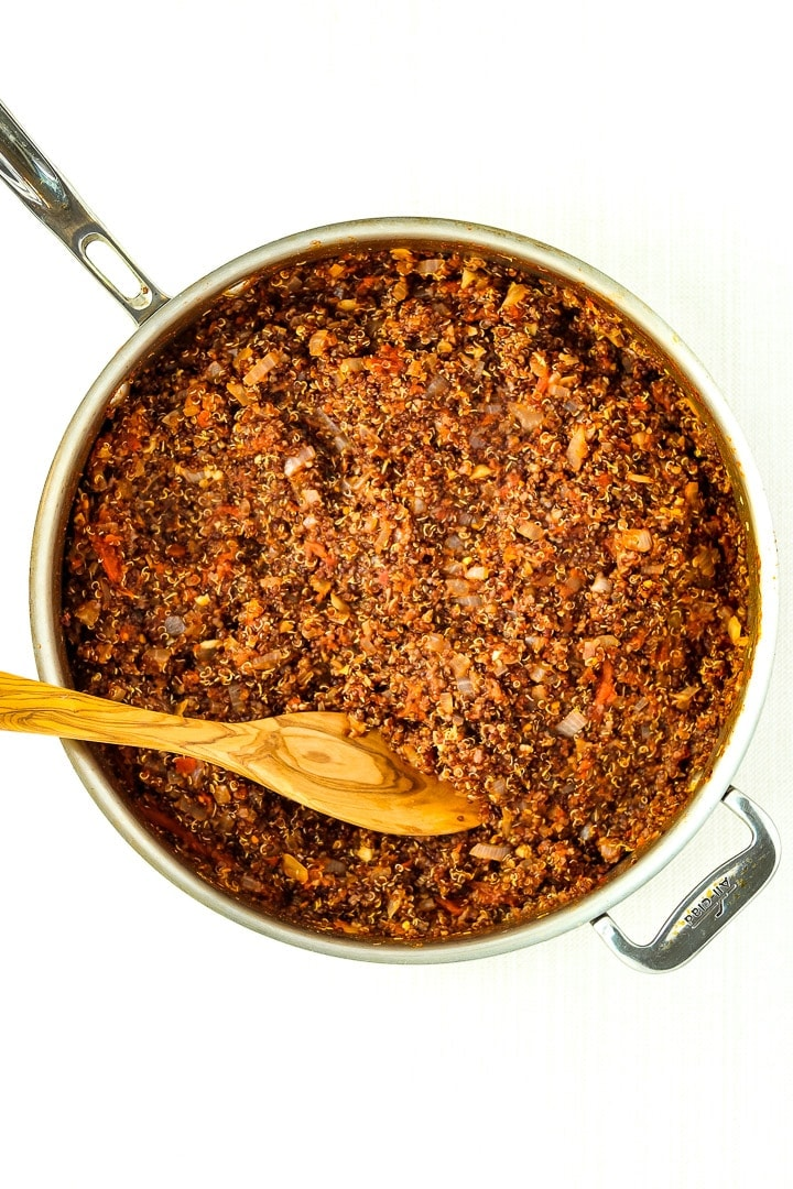 stainless steel skillet with cooked quinoa taco meat and wooden spoon.