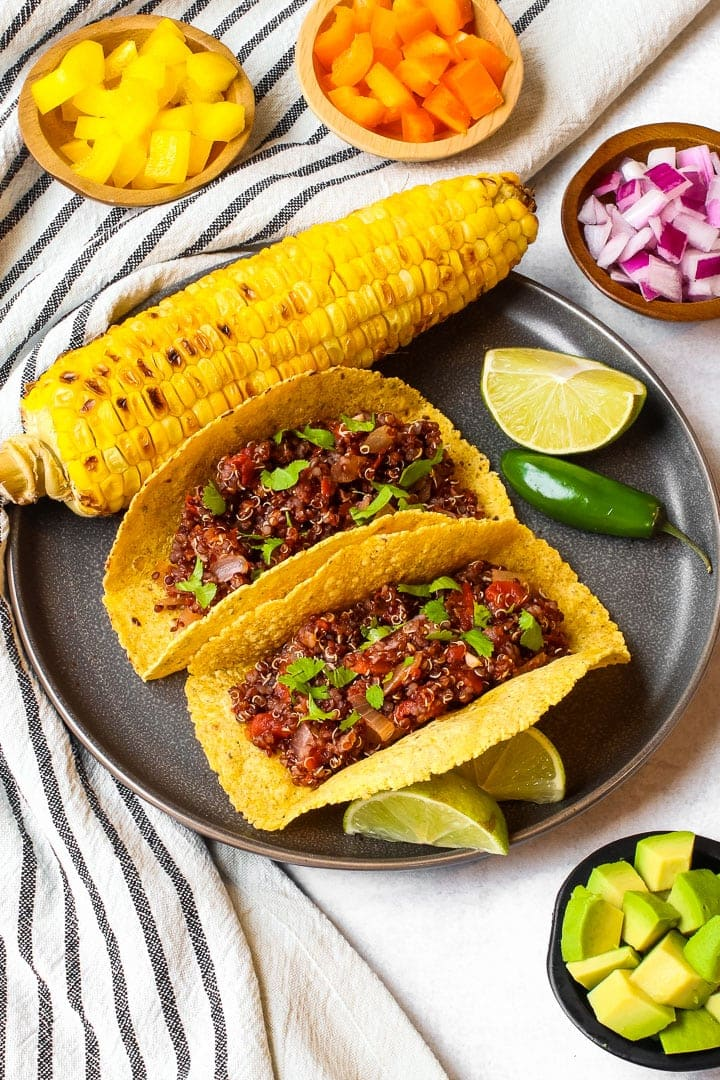 Tacos with red quinoa taco meat in corn tortilla shells on a fray plate with roasted ear of corn, lime and jalapeno, with small dishes of diced yellow and orange peppers, red onion and avocado on a napkin with black stripes.