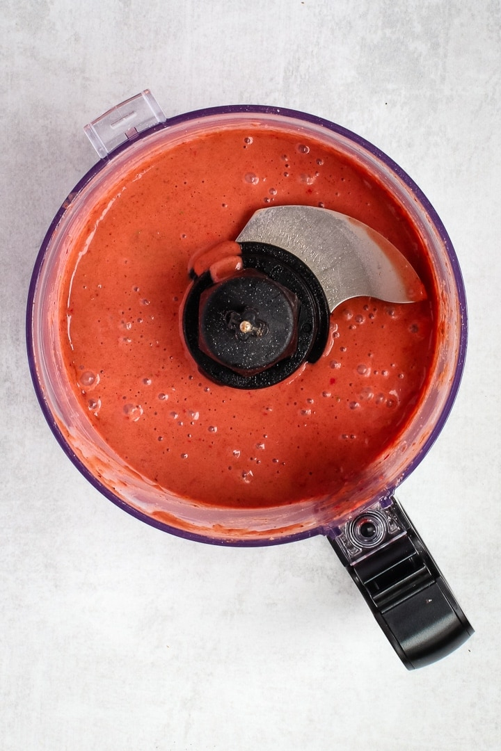 Strawberry balsamic vinaigrette in a food processor bowl on gray background.