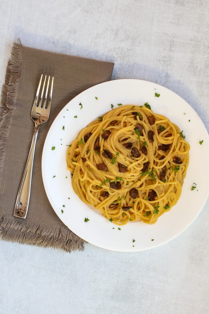 White plate of vegan spaghetti carbonara with mushroom bacon and parsley, with a brown napkin and fork on a gray background.