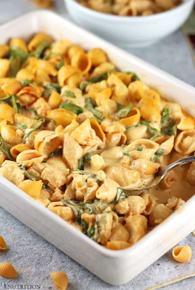 Small pasta shells with buffalo cheese sauce and herbs in a white rectangular baking dish with fork.