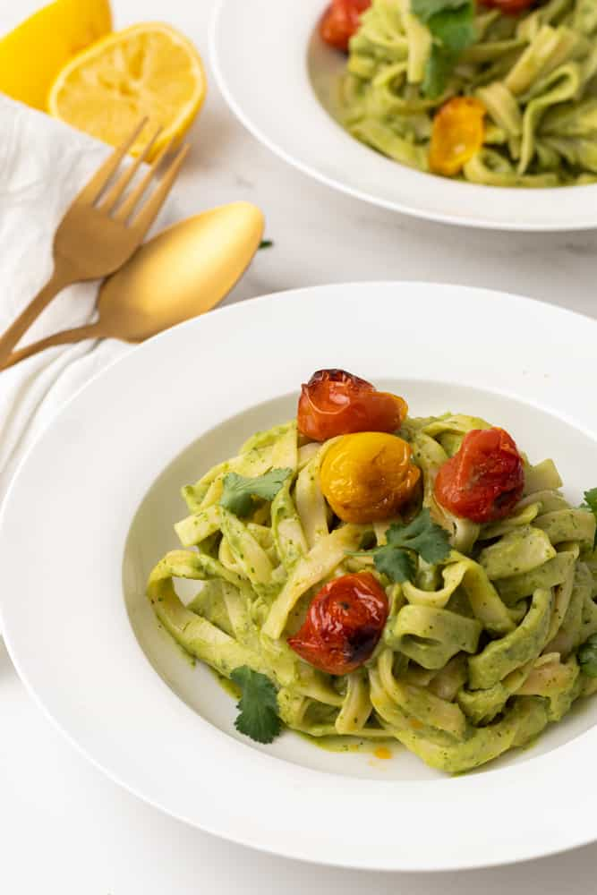 Fettuccine with green pasta sauce and blistered cherry tomatoes in a white dish. Gold knife and fork and lemon in background.