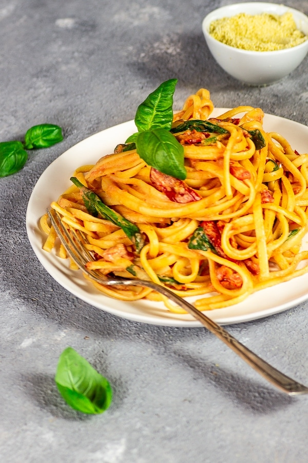 White plate with linguine with tomato alfredo sauce, with basil leaves, fork and vegan Warm in a white bowl.