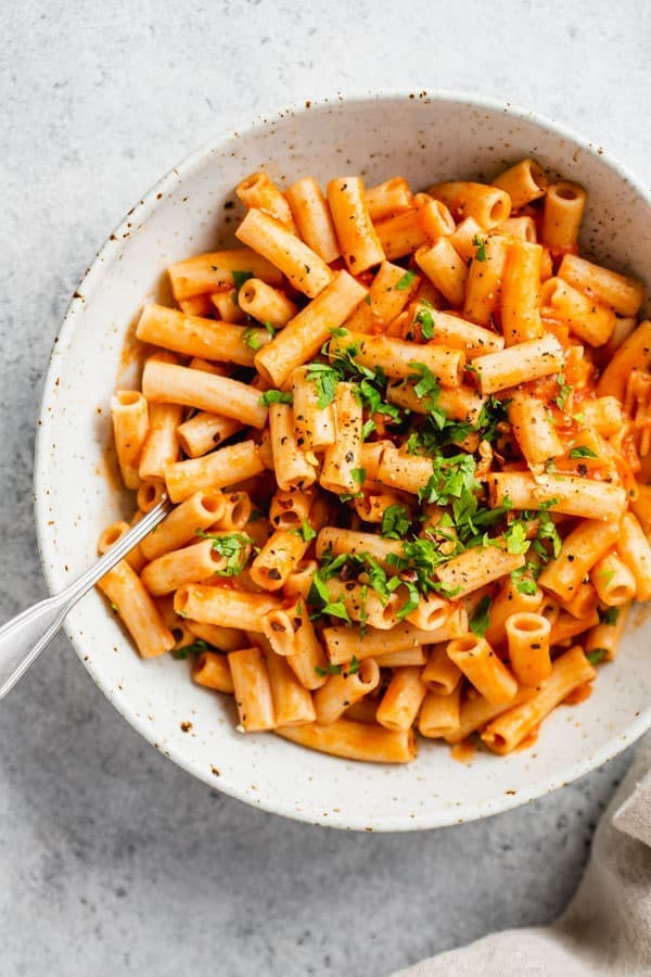 Flecked white bowl with creamy red pepper penne pasta, topped with herbs with fork.