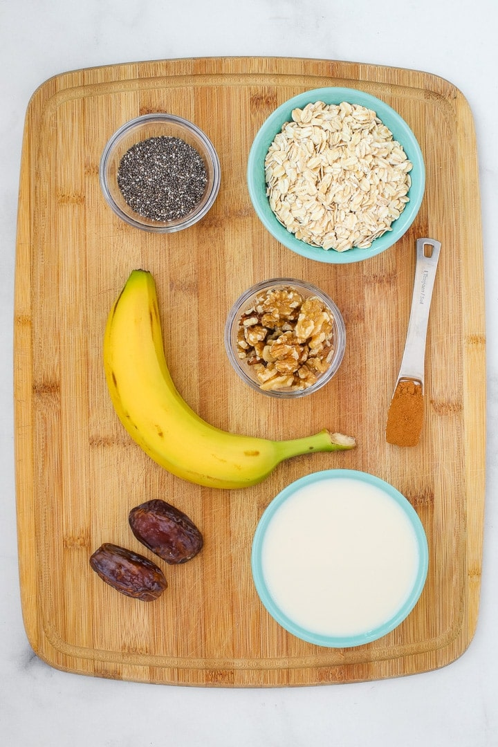 ingredients: rolled oats, plant milk, banana, chia seeds, walnuts, cinnamon and dates on a cutting board.