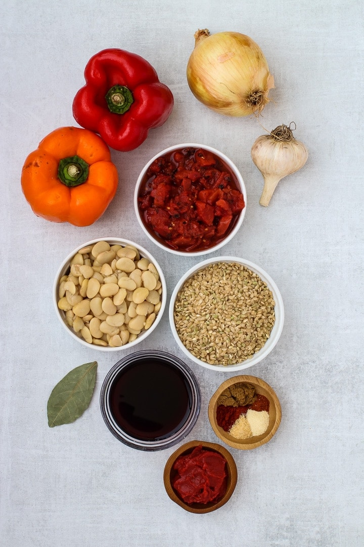 Red and orange bell peppers, yellow onion, garlic bulb, bay leaf, white dishes of butter beans, diced tomatoes, brown rice, and spices, red wine and tomato paste.