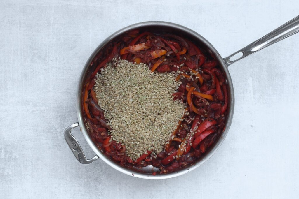 Step 3: After stirring in the tomato paste, add the spices and rice. Then deglaze with wine or sherry vinegar.