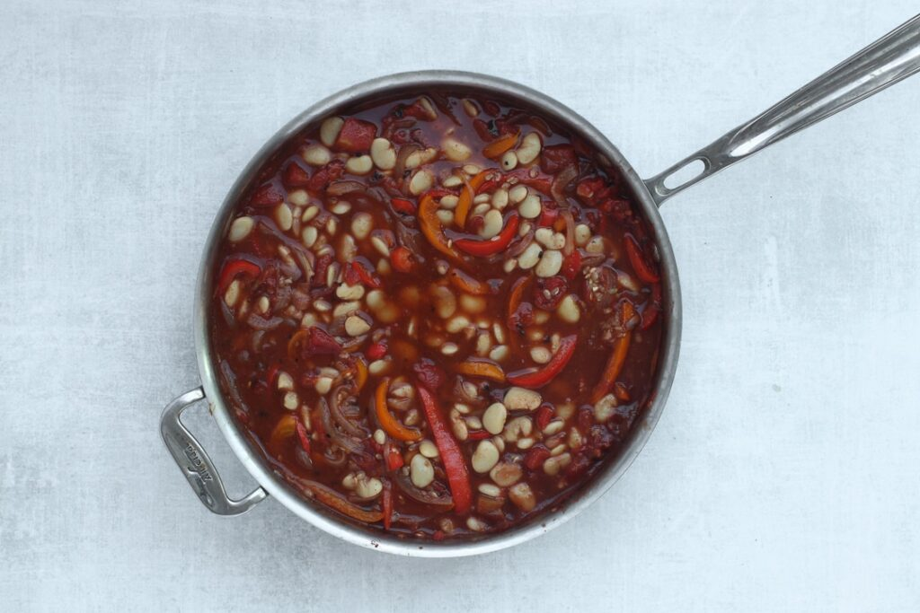 Step 4: Add the stock and beans to the skillet and simmer until rice is cooked.