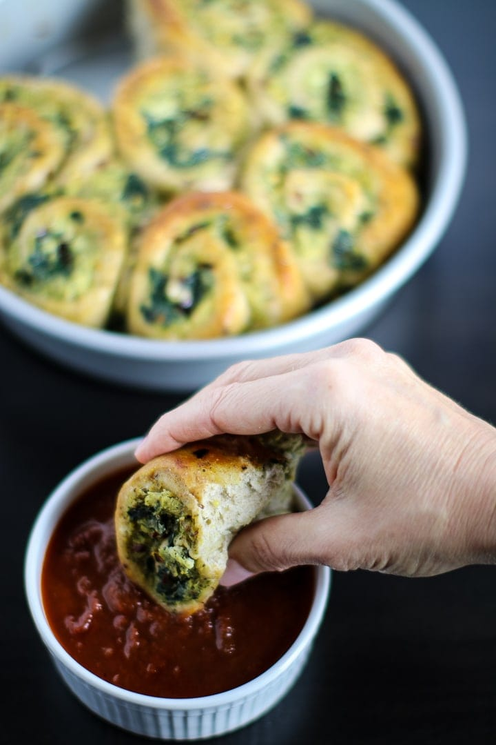 Spinach & Cheese Pizza Rolls in round baking pan and one being dipped in marinara sauce