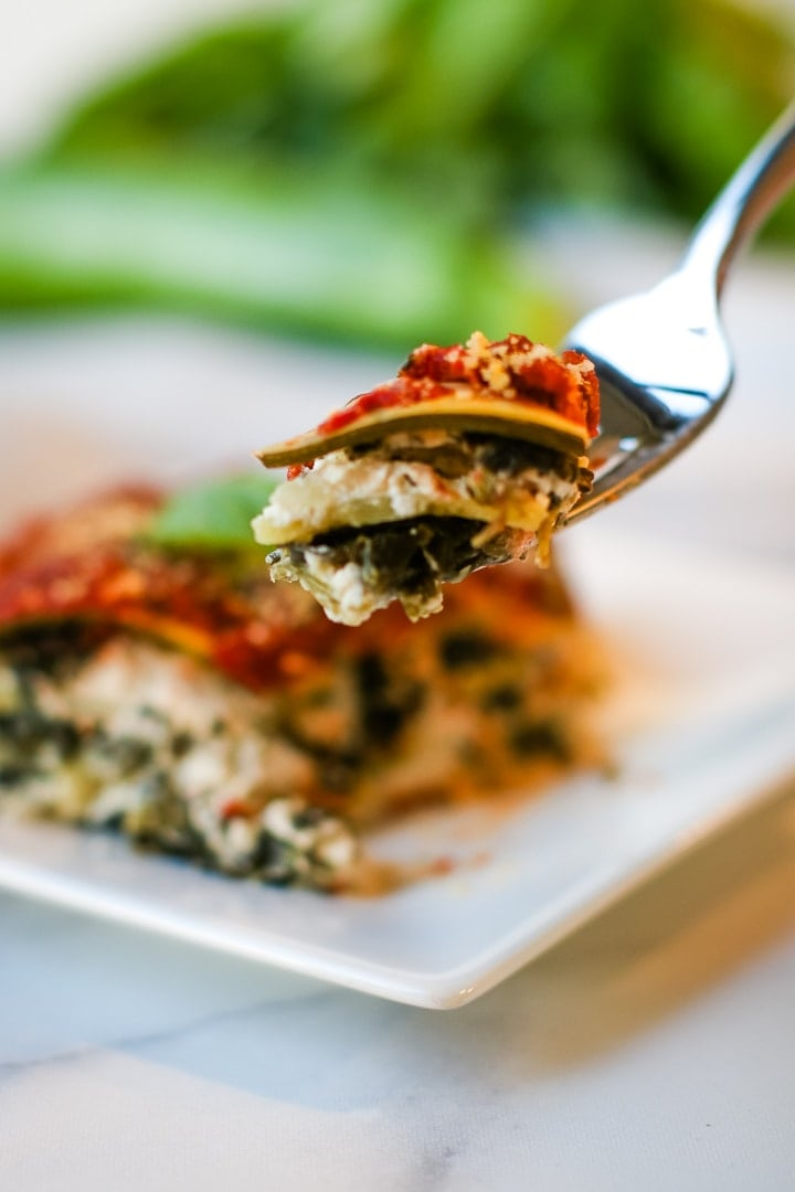 vegan zucchini lasagna bite on a fork, with plate of lasagna, zucchini and basil out of focus in background.