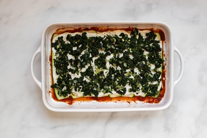 White baking dish with tomato sauce topped with zucchini slices and almond ricotta spread with Italian seasonings and spinach basil mixture on gray marble.