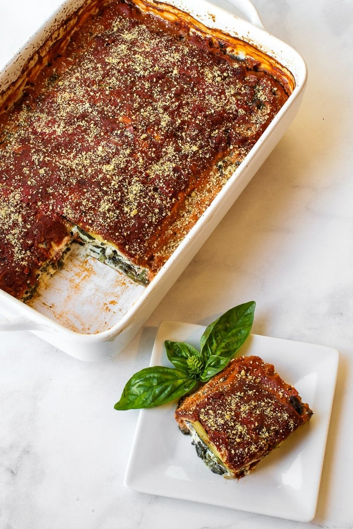 White baking dish with vegan Parmesan-topped baked lasagna, one piece cut and on a white plate with basil sprig, on gray marble.