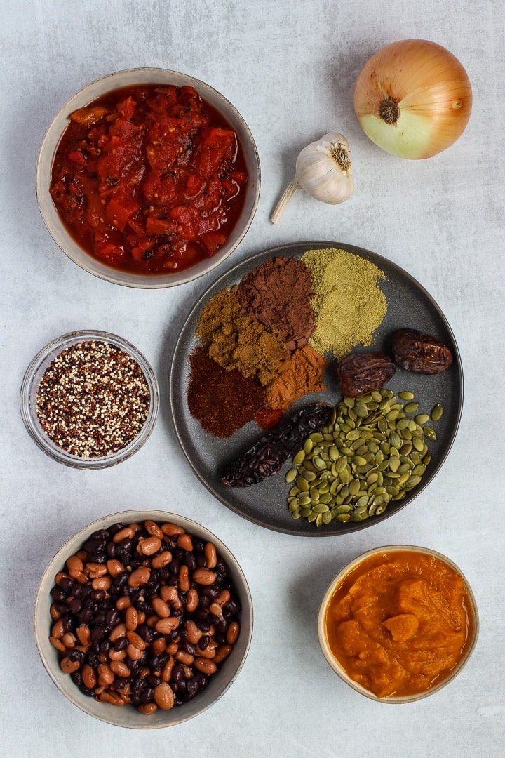 Pumpkin chile mole ingredients on a gray background: mole spices, pepita seeds, onion, garlic, black & pinto beans, tricolored quinoa, diced tomatoes, pumpkin puree.